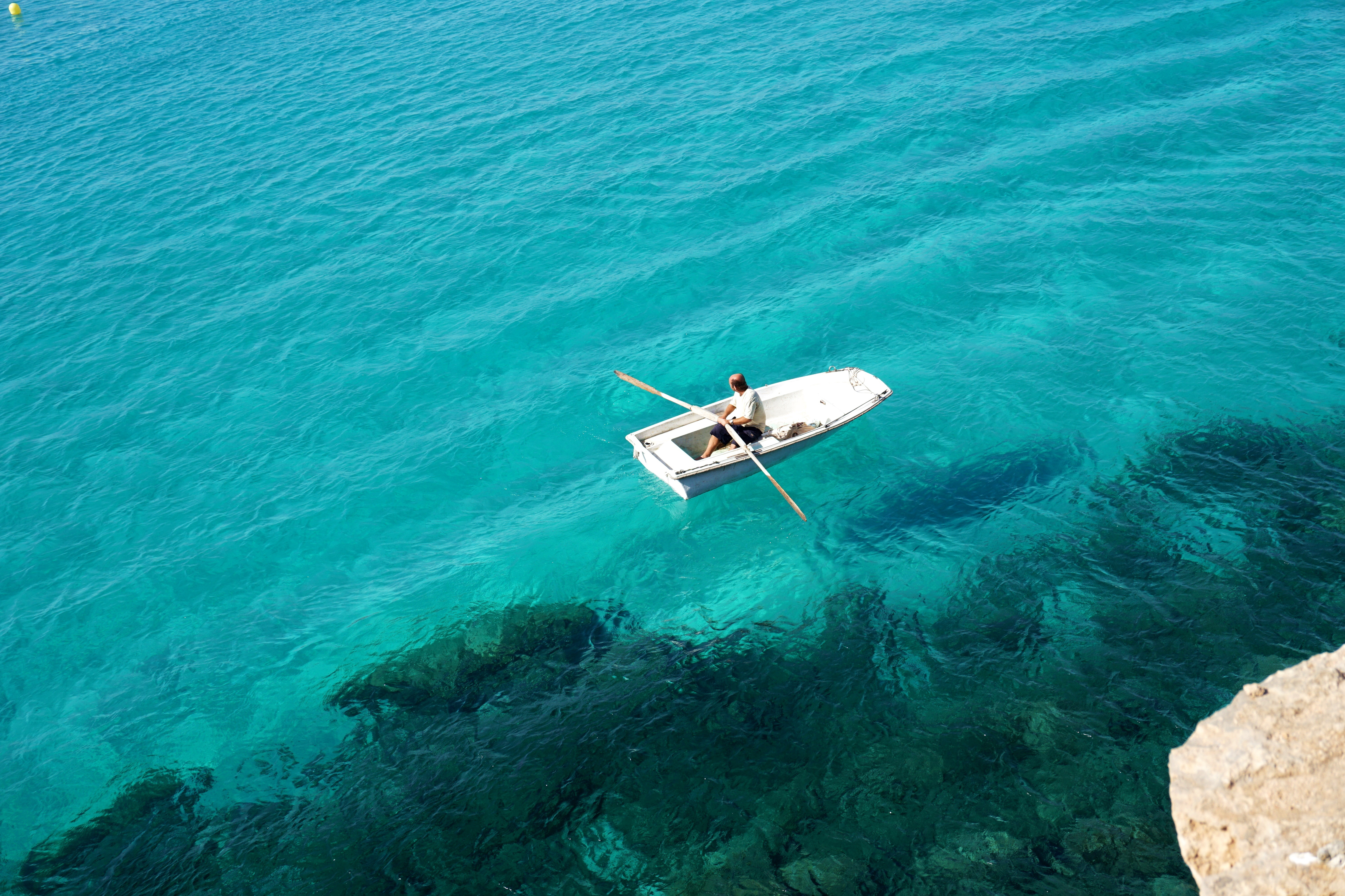 Man in little boat on the sea, rent a boat in Spain