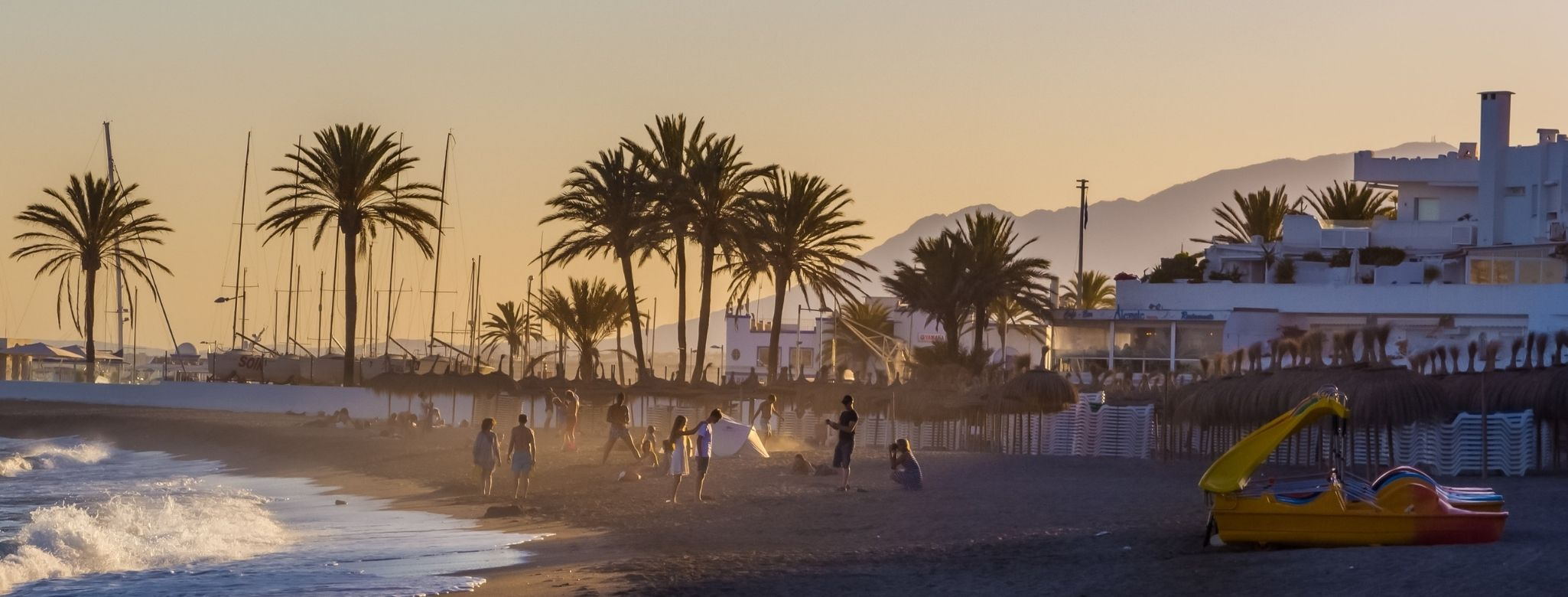people playing on the beach of Marbella with the palms and sunset on the background