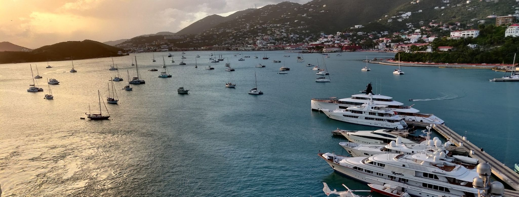 many boats and yachts sailing thorugh the US virgin islands on a sunset