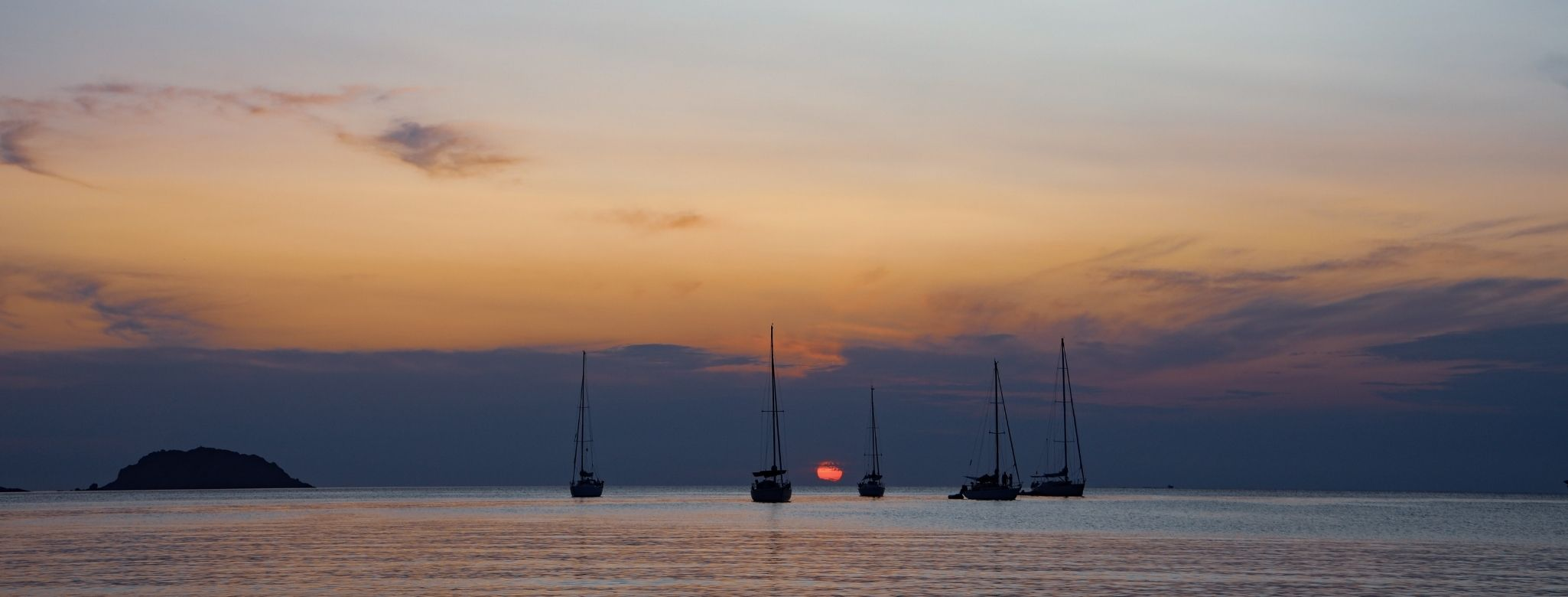 many boats anchoring in menorca on the sunset